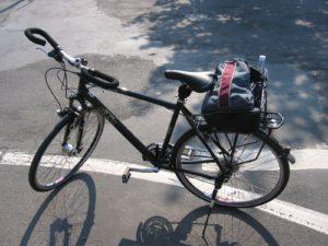 Das frisch gekaufte KTM Fahrrad, Totale, schaut nach links, steht auf Asphalt. Hat bereits Fahrradkorb und Rucksack drin, aber noch keine Getränkehalter und hat noch den alten Ständer hinten.