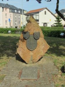 """Ein grosser Stein, mit dem Spruch """"Fir eis Fräiheet - Gescht Haut Mar"""", und den Wappen der Gemeinde Küntzig und Luxemburgs"""