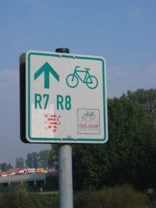 """Verkehrsschild auf dem Lahn Rad Weg. Aufschrift: Pfeil nach oben, drunter R7 R8, da drunter der Hessenlöwe. Rechts ein Fahrradsymbol mit Unterschrift """"DasLahntal"""". Im Hintergrung rechts Wald, links eine Autobahnbrücke (?)"""