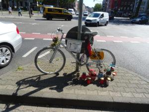 Ein nicht mehr fahrtüchtiges Fahrrad, weiss angestrichen angekettet am Hansemannplatz in Aachen. Vor dem Fahrrad stehen Kerzen. Im Hintergrund, Autos