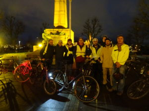 Posiertes Foto: 8 Personen in einer Reihe, vor ihnen mehrere Fahrräder, im Hintergrund der untere Teil der gëlle Fra. Alle winterlich gekleidet, die meisten in heller Kleidung, einige mit Fahrradhelm