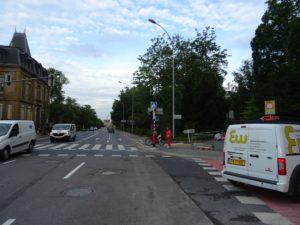 Eine Kreuzung mit abbiegendem Fahrzeug, Menschen an der Ampel für den Überweg und ein Schild zur Benutzung des Radweges auf dem Bürgersteig.