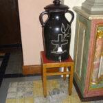 Ein schwarzes Porzellangefäss mit zwei Henkeln auf einem Stuhl. Auf dem Gefäss, ein Kreuz das in der rechten oberen Ecke von einer stylisierten Taube angeflogen wird