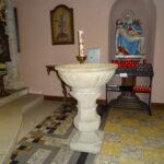 Der Taufstein, im Hintergrund in einer Nische die Siebenschmerzenmaria, davor ein Ständer mit Kerzen, links davon eine Osterkerze